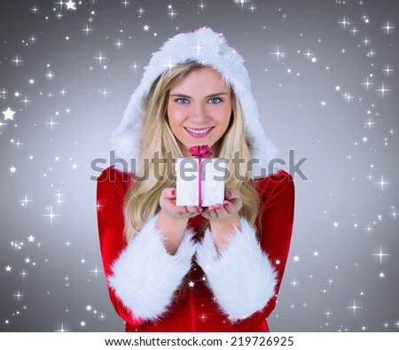 Pretty girl in santa outfit holding gift against grey vignette