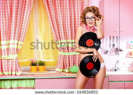 Pretty girl in sexy lingerie alluring with vinyl records on her glamorous pink kitchen. Fashion. Pin-up style. - stock photo
