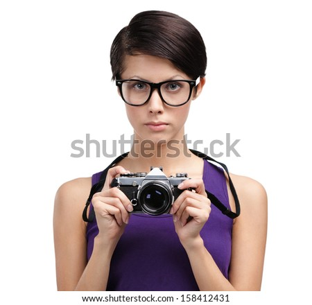 Pretty girl in spectacles hands retro photographic camera, isolated on white - stock photo