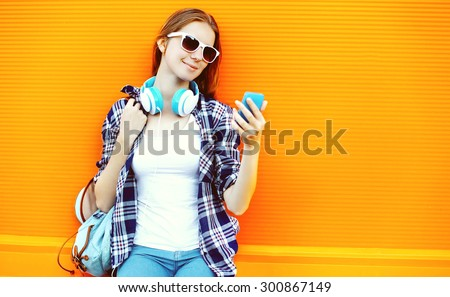 Pretty girl in sunglasses and headphones using smartphone against the colorful orange wall - stock photo