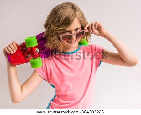 Pretty girl in sunglasses holding skateboard behind her head in studio against white background. - stock photo