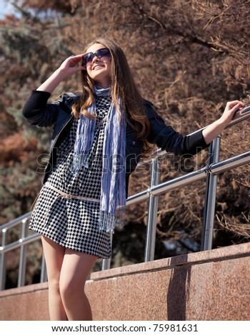 Pretty girl in sunglasses walks - stock photo