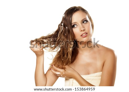 pretty girl in towel applied hair foam on white background - stock photo