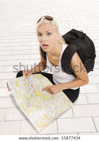 pretty girl in vacation with backpack sitting down with map and looking in camera surprised - stock photo
