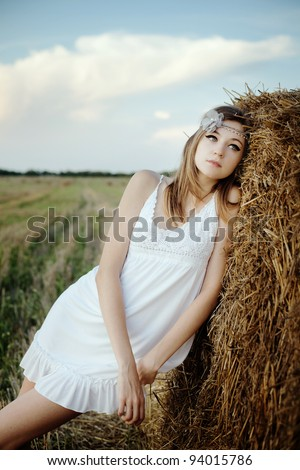 pretty girl in white dress standing behind haystacks - stock photo