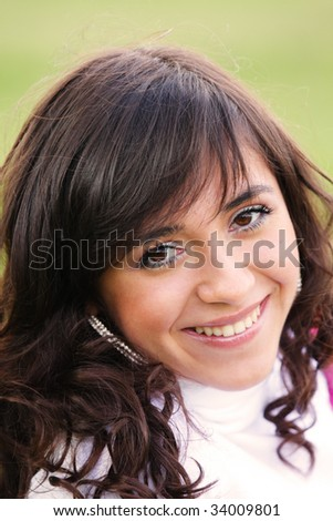Pretty girl in white smiles sincere outdoor portrait