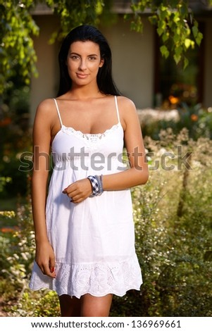Pretty girl in white summer dress standing in the garden, smiling.