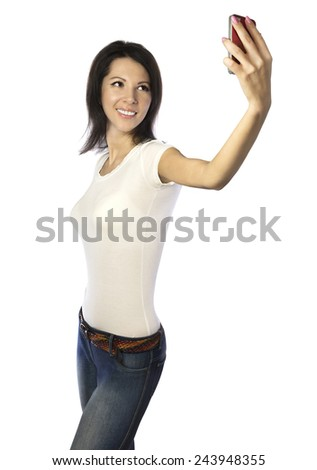Pretty girl in white t-shirt and jeans taking selfie photo with phone, isolated on white background - stock photo