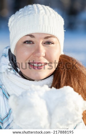 Pretty girl in winter clothing with full guest snow in hands in mittens - stock photo
