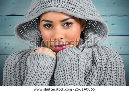 Pretty girl in winter jumper looking at camera against painted blue wooden planks - stock photo