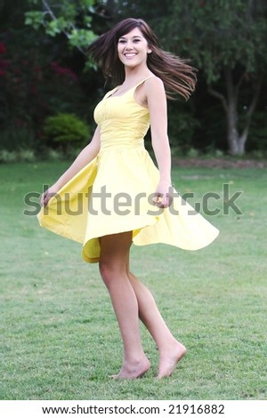 Pretty girl in yellow dress dancing on green grass