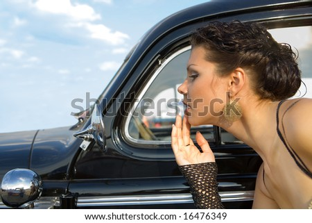 Pretty girl is fixing her make-up near the vintage car.