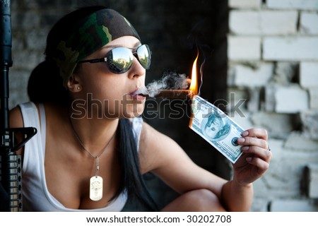 Pretty girl is lighting a cigar from one hundred dollars bill.