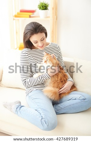 Pretty girl is playing with her pet - stock photo