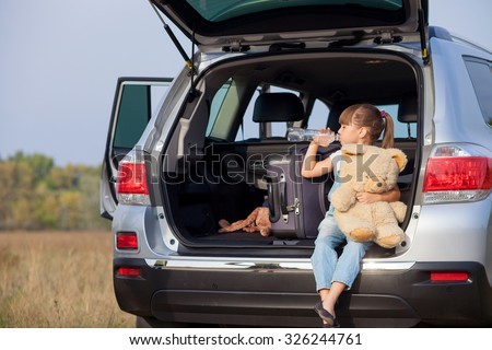 Pretty girl is sitting on open car boot in the nature. She is holding bottle and drinking water. Her eyes are closed with pleasure. The kid is holding teddy bear - stock photo