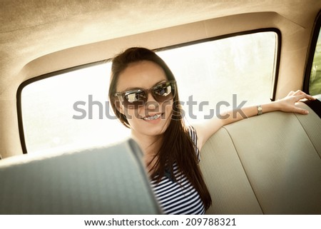 Pretty girl is sitting on the back seat of a car, wearing sunglasses - stock photo
