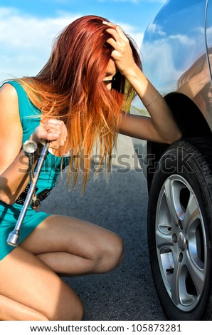 Pretty girl is trying to change a tire on a road - stock photo