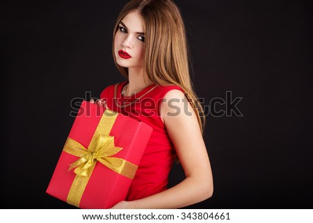 Pretty girl is wearing red dress holding gift box. Smiling beautiful woman portrait isolated on black background. - stock photo