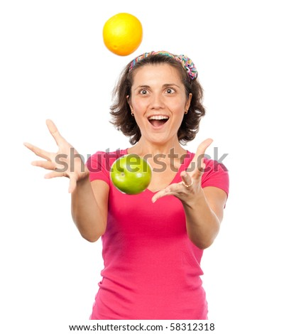 Pretty girl juggling oranges and apples - stock photo