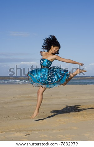 Pretty girl jumping wearing a puffy blue dress - stock photo