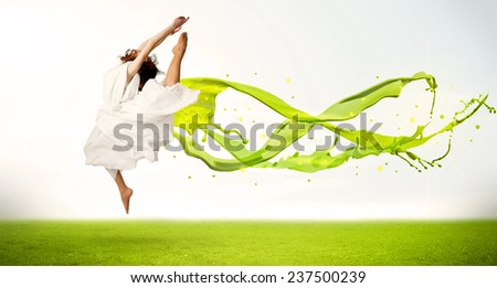 Pretty girl jumping with green abstract liquid dress concept in nature - stock photo