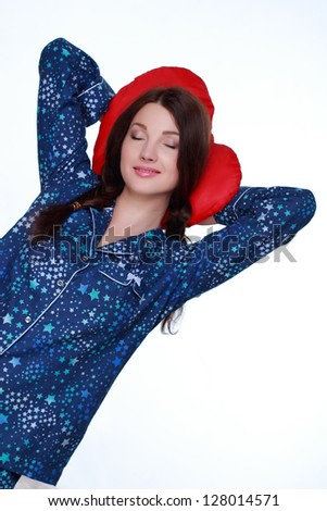 Pretty girl keeps a red pillow in blue pajamas in the form of heart on white background on Holiday theme