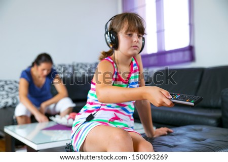 Pretty girl listening to music with headphones  in the living room and holding remote control - stock photo