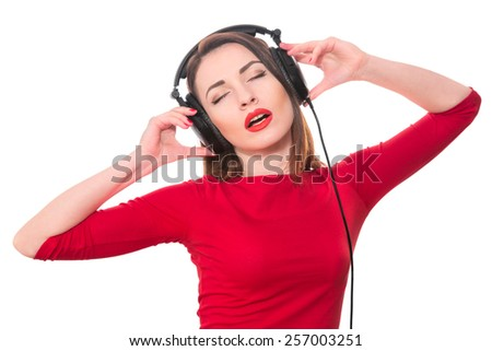 Pretty girl listening to the music with closed eyes touching big headphones isolated on white background - stock photo
