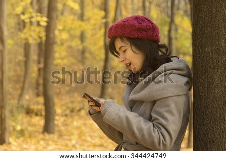 Pretty girl looking at her smartphone in the woods