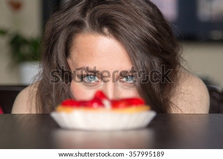 Pretty girl Looking to strawberry cake in living room