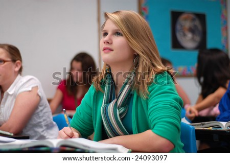 Pretty girl looking up in a classroom and taking notes