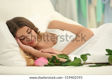 Pretty girl lying in bed with pink rose