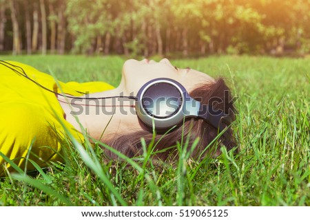 pretty girl lying in summer grass with headphones listening to music and relaxing