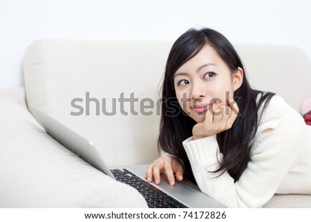 Pretty girl lying on a sofa with notebook computer. - stock photo