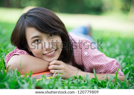 Pretty girl lying on grass and looking at camera