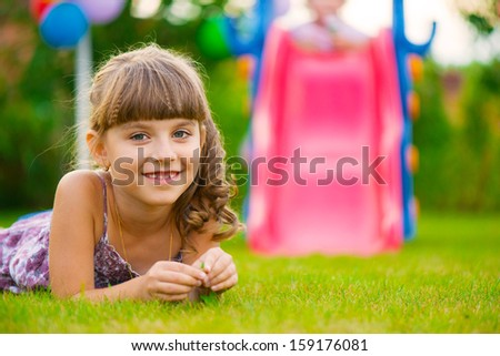 Pretty girl lying on green grass at playground - stock photo