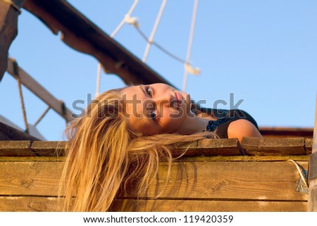 Pretty girl lying on the deck of an old wooden ship