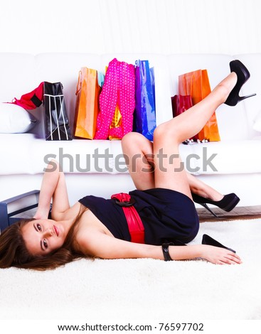 Pretty girl lying. Shopping bags placed on the sofa - stock photo