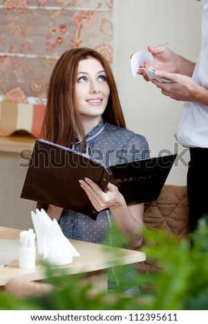 Pretty girl makes an order. The waiter listens to her attentively and white down everything - stock photo