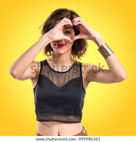 Pretty girl making a heart with her hands over yellow backgound