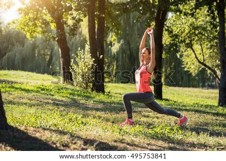 Pretty girl making lunges during her outdoors training