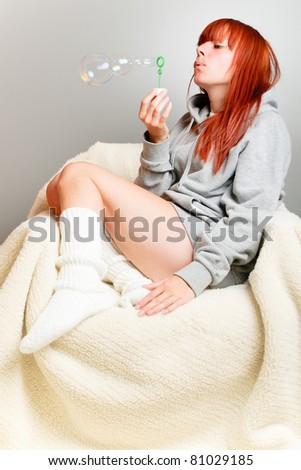 Pretty girl making soap bubbles - stock photo