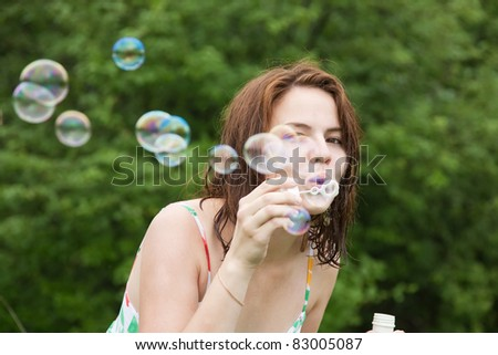Pretty girl making soap bubbles against trees