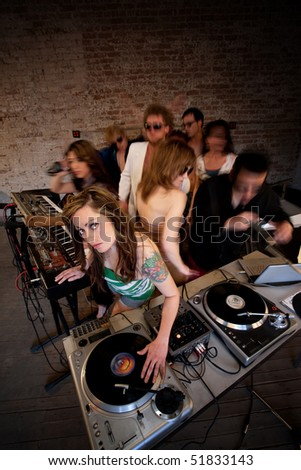 Pretty girl mixing music at a 1970s disco party - stock photo