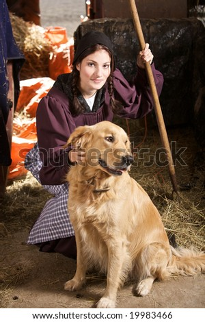 Pretty girl on a farm with her golden retriever that is out of focus - stock photo