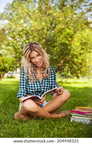 Pretty girl on a grass with the books