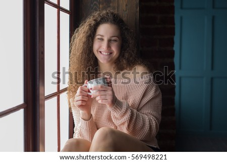 Pretty girl on a windowsill with cup in her hands