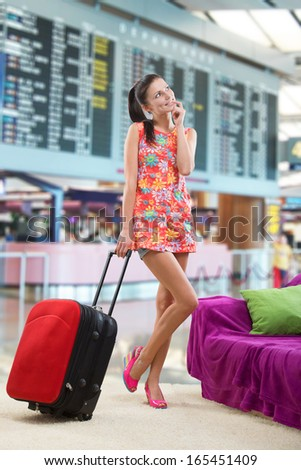 Pretty girl planning her travel abroad, against a background of a departure board  - stock photo