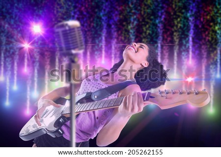 Pretty girl playing guitar against digitally generated bright firework design - stock photo
