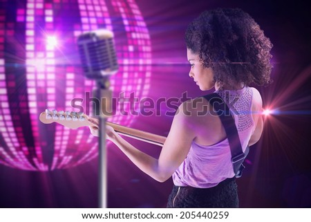 Pretty girl playing guitar against digitally generated cool disco ball design - stock photo